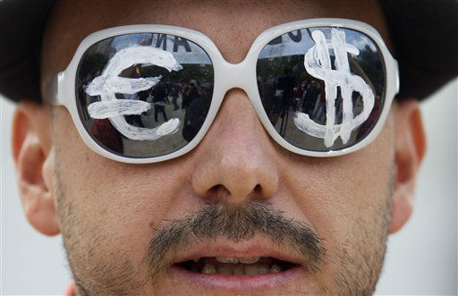 A protester wears glasses with the euro and dollar symbols painted on the lenses before a protest march in Madrid, Tuesday Sept. 25, 2012.  Thousands of people are expected to converge on the Spanish Parliament to protest the conservative government&#39;s handling of the economic crisis and to demand fresh elections. Organizers of the &#39;Occupy Congress&#39; protest hope to form a protest chain around the building but heavy police reinforcements are likely to keep them well away. &#40;AP Photo&#47;Paul White&#41; <span class=meta>(AP Photo&#47; Paul White)</span>