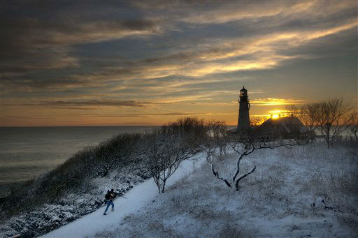 Clearing skies await a tripod-toting photographer looking for a spot to capture the early-morning light at Portland Head Light, Thursday, Jan. 17, 2013, in Cape Elizabeth, Maine. A snowstorm that ended before dawn temporarily transformed Fort Williams Park into a snowy scene. (AP Photo/Robert F. Bukaty)