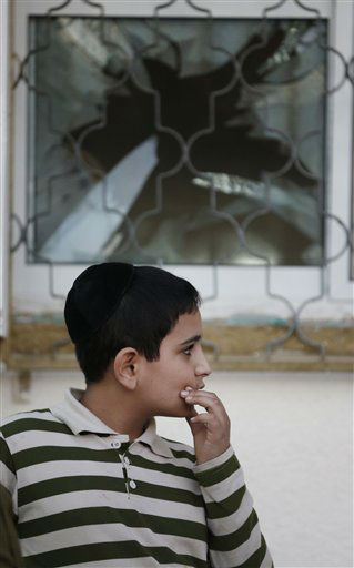 A child looks at damages of a house after a rocket fired by Palestinian militants from inside the Gaza Strip, landed at the community of Ofakim, in southern Israel, Sunday, Nov. 18, 2012. Israel launched the operation last Wednesday by assassinating Hamas? military chief and carrying out dozens of airstrikes on rocket launchers and weapons storage sites. Over the weekend, the operation began to target Hamas government installations as well, including the offices of its prime minister and attacks on a major training base and the two media centers.  &#40;AP Photo&#47;Lefteris Pitarakis&#41; <span class=meta>(AP Photo&#47; Lefteris Pitarakis)</span>