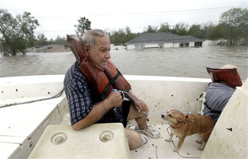 Carlo Maltese and his dog Pin ride in a boat after being rescued from his flooded home as Hurricane Isaac hits Wednesday, Aug. 29, 2012, in Braithwaite, La. &#40;AP Photo&#47;David J. Phillip&#41; <span class=meta>(AP Photo&#47; David J. Phillip)</span>