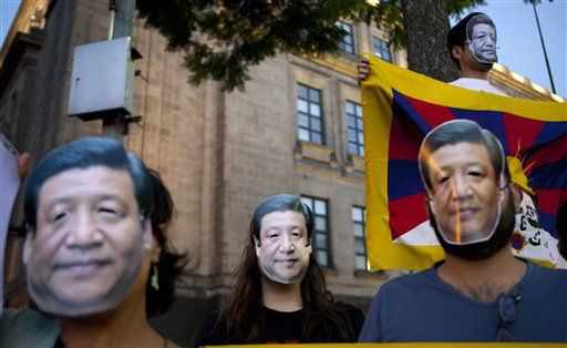 Supporters of a free Tibet wear masks of China&#39;s President Xi Jinping and hold a Tibetan flag to protest Xi&#39;s visit outside the National Palace where he is attending a dinner in Mexico City, Tuesday, June 4, 2013. Xi is in Mexico for a three day visit. &#40;AP Photo&#47;Eduardo Verdugo&#41; <span class=meta>(AP Photo&#47; Eduardo Verdugo)</span>