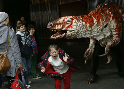 Children react as a carnivorous theropod known as the Australovenator dinosaur walks through crowds along the Southbank, in London, Monday, Feb. 18, 2013. The dinosaur is one of many that can be visited at the Erth&#39;s Dinosaur Petting Zoo, visiting from Australia, the creatures can be touched and fed at the Southbank Centre. &#40;AP Photo&#47;Kirsty Wigglesworth&#41; <span class=meta>(AP Photo&#47; Kirsty Wigglesworth)</span>