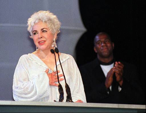 Hollywood legend Elizabeth Taylor acknowledges the standing ovation she receives after walking onto the runway at Macy&#39;s Passport &#39;97 &#34;Fusion,&#34; which raises funds for the fight against HIV and AIDS, Thursday, Sept. 18, 1997, in San Francisco.  Earvin &#34;Magic&#34; Johnson, who is hosting the opening night gala of Macy&#39;s Passport &#39;97 with Taylor, claps with the audience.  &#40;AP Photo&#47;Robin Weiner&#41; <span class=meta>(AP Photo&#47; ROBIN WEINER)</span>