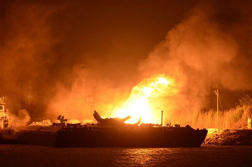 A massive explosion at 3a.m. EDT on one of the two barges still ablaze in the Mobile River in Mobile, Ala., on Thursday, April 25, 2013. Three people were injured in the blast. Fire officials have pulled units back from fighting the fire due to the explosions and no immediate threat to lives. &#40;AP Photo John David Mercer&#41; <span class=meta>(AP Photo&#47; John David Mercer)</span>