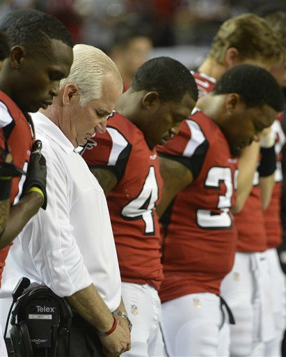 Atlanta Falcons head coach Mike Smith, second from left, and players close their eyes during during a moment of silence for the victims of the Sandy Hook Elementary School shootings before an NFL football game against the New York Giants, Sunday, Dec. 16, 2012, in Atlanta. A gunman walked into the school in Newtown, Conn., Friday and opened fire, killing 26 people, including 20 children. &#40;AP Photo&#47;Rich Addicks&#41; <span class=meta>(AP Photo&#47; Rich Addicks)</span>