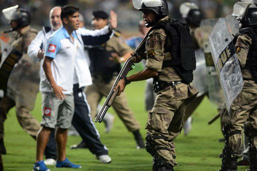 Brazilian anti-riot police take the field holding rubber bullet guns during clashes with soccer players from Argentina&#39;s Arsenal at the end of their Copa Libertadores soccer match with Brazil&#39;s Atletico Mineiro in Belo Horizonte, Brazil, Wednesday, April 3, 2013.  At least four players from Argentine club Arsenal were detained for interrogation after a confrontation with Brazilian police. Police said at least two officers and a journalist sustained minor injuries in the brawl after Atletico Mineiro&#39;s 5-2 win over the Argentine club Arsenal. Authorities said the players will likely be charged after throwing punches and kicking police officers who were trying to protect the referees as the final whistle blew. &#40;AP Photo&#47;Eugenio Savio&#41; <span class=meta>(AP Photo&#47; Eugenio Savio)</span>