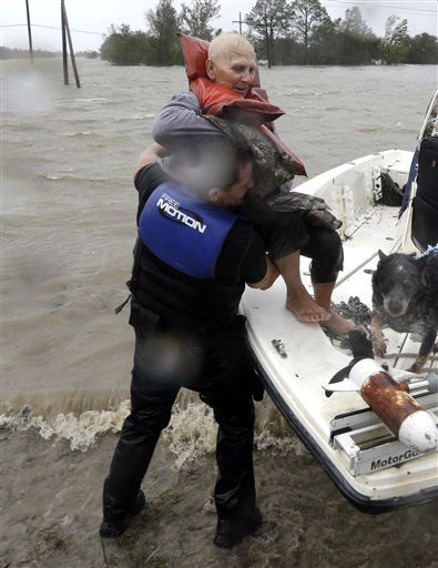 Elaine Maltese is lifted out of a boat by by Drug Enforcement Agency Special Agent Keith Billiot, left, after being rescued from her flooded home as Hurricane Isaac hits Wednesday, Aug. 29, 2012, in Braithwaite, La. &#40;AP Photo&#47;David J. Phillip&#41; <span class=meta>(AP Photo&#47; David J. Phillip)</span>