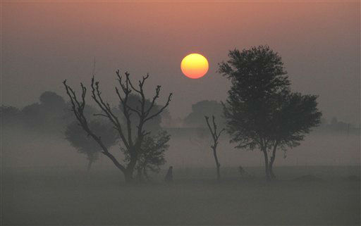 An Indian walks surrounded by fog as the sun rises in Ajmer, India, Tuesday, Jan. 1, 2013. North India continues to face extreme weather conditions with dense fog affecting flights and trains. &#40;AP Photo&#47;Deepak Sharma&#41; <span class=meta>(AP Photo&#47; Deepak Sharma)</span>