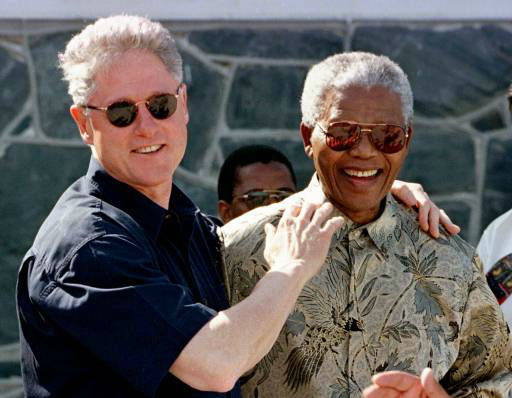 "<div class=""meta image-caption""><div class=""origin-logo origin-image ""><span></span></div><span class=""caption-text"">U.S. President Bill Clinton and South African President Nelson Mandela laugh together on a tour of Robben Island, South Africa Friday, March 27, 1998. Mandela spent the afternoon showing Clinton the penal colony where he was held for 18 years by the former South African government. (AP Photo/Pool, Rick Wilking) (AP Photo/ RICK WILKING)</span></div>"