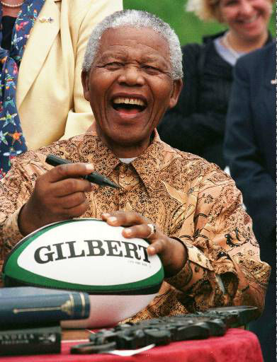 South African President Nelson Mandela prepares to autograph a rugby ball at the request of a youngster at Cardiff Castle Tuesday June 16, 1998. The Welsh, proud of organizing small local boycotts when Britain and the rest of the EU refused to impose punitive trade embargos on apartheid South Africa, gave Mandela the freedom, or key, of their capital. &#40;AP Photo&#47;Louisa Buller, WPA POOL&#41; <span class=meta>(AP Photo&#47; LOUISE BULLER)</span>