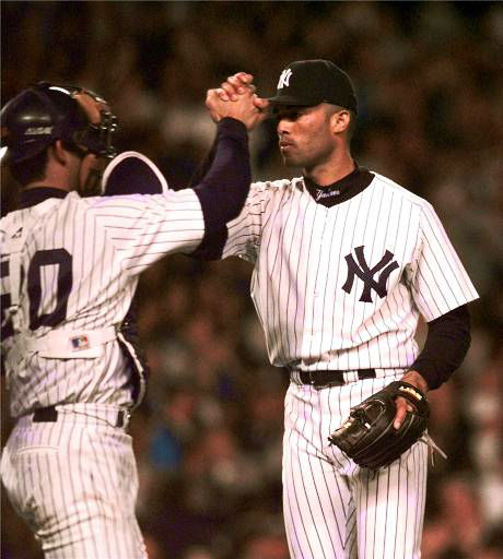 New York Yankees reliever Mariano Rivera, right, high fives catcher Jorge Posada after the Yankees beat Texas Rangers 2-0 in game one of the 1998 Division Series at Yankee Stadium Tuesday, Sept. 29, 1998 in New York. &#40;AP Photo&#47;Kathy Willens&#41; <span class=meta>(AP Photo&#47; KATHY WILLENS)</span>