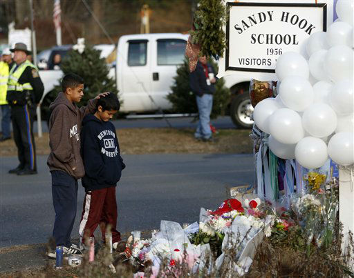 Brothers Thomas, 13, left, and Steven Leuci, 9, pay their respects at a memorial for shooting victims near Sandy Hook Elementary School, Saturday, Dec. 15, 2012 in Newtown, Conn.  A gunman walked into Sandy Hook Elementary School in Newtown Friday and opened fire, killing 26 people, including 20 children. &#40;AP Photo&#47;Jason DeCrow&#41; <span class=meta>(AP Photo&#47; Jason DeCrow)</span>