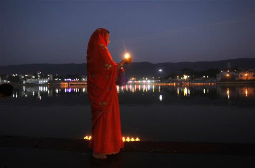 In this Wednesday, Nov. 21, 2012 photo, an Indian Hindu devotee holds a traditional oil lamp as she performs evening prayers near the Pushkar Lake during the annual cattle fair at Pushkar, Rajasthan, India. Pushkar, located on the banks of the Pushkar Lake, is a popular Hindu pilgrimage spot that is also frequented by foreign tourists who come to the town for the annual cattle fair and camel races. &#40;AP Photo&#47;Rajesh Kumar Singh&#41; <span class=meta>(AP Photo&#47; Rajesh Kumar Singh)</span>