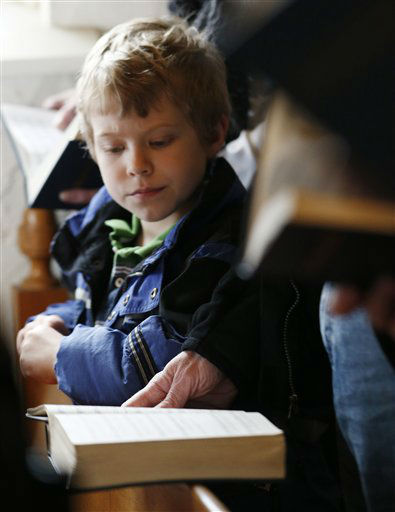 A child looks on as people read from prayer books during a service in honor of the victims who died a day earlier when a gunman opened fire at Sandy Hook Elementary School in Newtown, Conn., as people gathered at St. John&#39;s Episcopal Church , Saturday, Dec. 15, 2012, in the Sandy Hook village of Newtown, Conn.  The massacre of 26 children and adults at Sandy Hook Elementary school elicited horror and soul-searching around the world even as it raised more basic questions about why the gunman, 20-year-old Adam Lanza, would have been driven to such a crime and how he chose his victims. &#40;AP Photo&#47;Julio Cortez&#41; <span class=meta>(AP Photo&#47; Julio Cortez)</span>