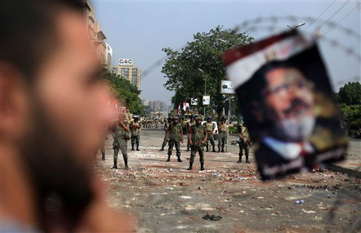 A protester stands next to a poster of ousted President Mohammed Morsi hanged on the barb wire as army soldiers guard at the Republican Guard building in Nasr City, Cairo, Egypt, Tuesday, July 9, 2013. Egyptian security forces killed dozens of supporters of Egypt&#39;s ousted president in one of the deadliest single episodes of violence in more than two and a half years of turmoil. The toppled leader&#39;s Muslim Brotherhood called for an uprising, accusing troops of gunning down protesters, while the military blamed armed Islamists for provoking its forces. &#40;AP Photo&#47;Khalil Hamra&#41; <span class=meta>(AP Photo&#47; Khalil Hamra)</span>