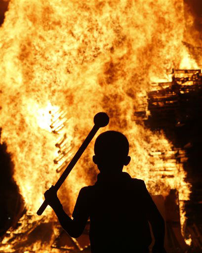 A boy watches a bonfire in the Protestant Sandy Row area of Belfast, Northern Ireland, Thursday, July 11, 2013.  Hundreds of fires were set alight Thursday as loyalists celebrate The Twelfth, the holiday remembering the defeat of the Catholic King James, by the Protestant William of Orange in 1690. &#40;AP Photo&#47;Peter Morrison&#41; <span class=meta>(AP Photo&#47; Peter Morrison)</span>