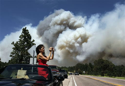 Colorado Springs resident Yolette Baca takes a photo of the wildfire in the Black Forest area north of Colorado Springs, Colo., on Wednesday, June 12, 2013. The number of houses destroyed by the Black Forest fire could grow to around 100, and authorities fear it&#39;s possible that some people who stayed behind might have died. &#40;AP Photo&#47;Brennan Linsley&#41; <span class=meta>(AP Photo&#47; Brennan Linsley)</span>