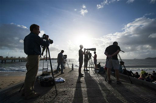 In this photo released by Tourism Queensland, people gather on a beach at Palm Cove in Queensland state, Australia, to watch and photograph a total solar eclipse Wednesday, Nov. 14, 2012. Starting just after dawn, the eclipse cast its 150-kilometer &#40;95-mile&#41; shadow in Australia&#39;s Northern Territory, crossed the northeast tip of the country and was swooping east across the South Pacific, where no islands are in its direct path. &#40;AP Photo&#47;Tourism Queensland, Murray Anderson-Clemence&#41; EDITORIAL USE ONLY <span class=meta>(AP Photo&#47; Murray Anderson-Clemence)</span>