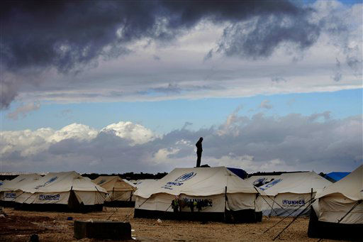 A Syrian refugee stands on top of a water tank at Zaatari refugee camp, near the Syrian border in Mafraq, Jordan, Wednesday, Jan. 9, 2013. The unusual weather was a particularly harsh blow for the vulnerable Syrian refugees, especially about 50,000 sheltering in the Zaatari tent camp in Jordan&#39;s northern desert. Torrential rains over the past four days have flooded 200 tents and forced women and infants to evacuate in temperatures below freezing at night, whipping wind and lashing rain. &#40;AP Photo&#47;Mohammad Hannon&#41; <span class=meta>(AP Photo&#47; Mohammad Hannon)</span>