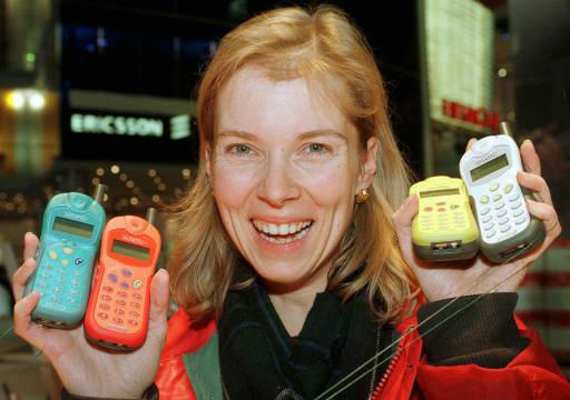 A trade fair hostess from Geneva, shows mobile phones at the Alcatel stand before the opening of  the &#39;Telecom 99&#39; and &#39;Interactive 99&#39; exhibition in Geneva, Switzerland, Thursday October 7, 1999. The world biggest telecomunication fair  will open  October 10. &#40;AP PHOTO&#47;Martial Trezzini&#47;KEYSTONE&#41; <span class=meta>(AP Photo&#47; MARTIAL TREZZINI)</span>