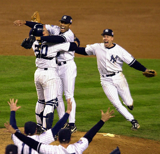 New York Yankees catcher Jorge Posada, left rear, and third baseman Scott Brosius, right rear, rush pitcher Mariano Rivera as teammates run to the mound after the Yankees beat the Atlanta Braves 4-1 in Game 4 to sweep the World Series Wednesday, Oct. 27, 1999, in New York. Rivera was named the Most Valuable Player of the series. &#40;AP Photo&#47;Ron Frehm&#41; <span class=meta>(AP Photo&#47; RON FREHM)</span>