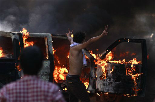 "<div class=""meta ""><span class=""caption-text "">An Egyptian protester flashes the victory sign next to a burning police car during clashes near the U.S. embassy in Cairo, Egypt, Thursday, Sept. 13, 2012. Protesters clashed with police near the U.S. Embassy in Cairo for the third day in a row. Egypt's Islamist President Mohammed Morsi vowed to protect foreign embassies in Cairo, where police were using tear gas to disperse protesters at the U.S. mission. (AP Photo/Khalil Hamra) (AP Photo/ Khalil Hamra)</span></div>"