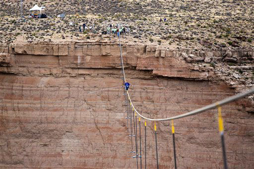 Aerialist Nik Wallenda pauses during his quarter mile walk over the Little Colorado River Gorge in northeastern Arizona on Sunday, June 23, 2013. The daredevil successfully traversed a tightrope strung 1,500 feet above the chasm near the Grand Canyon in just more than 22 minutes, pausing and crouching twice as winds whipped around him and the cable swayed. &#40;AP Photos&#47;Discovery Channel, Tiffany Brown&#41; <span class=meta>(AP Photo&#47; Tiffany Brown)</span>
