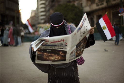 An Egyptian woman reads the newspaper after spending the night in Tahrir Square in downtown Cairo, Egypt , Saturday, Feb. 12, 2011. Cries of &#34;Egypt is free&#34; rang out and fireworks lit up the sky as hundreds of thousands danced, wept and prayed in joyful pandemonium after 18 days of peaceful pro-democracy protests forced President Hosni Mubarak to surrender power to the military, ending three decades of authoritarian rule.  &#40;AP Photo&#47;Emilio Morenatti&#41; <span class=meta>(AP Photo&#47; Emilio Morenatti)</span>