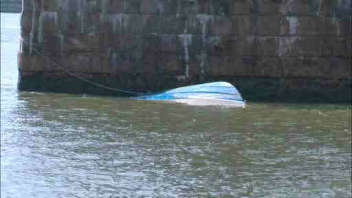 Three people were rescued after a 25 foot boat capsized in the East River just under the Manhattan Bridge.