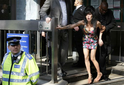 British singer Amy Winehouse is assisted as she leaves Westminster Magistrates Court in London, Tuesday, March 17, 2009, where she pleaded not guilty to a charge of common assault, over an incident at a charity ball.  Winehouse, 25, is accused of attacking a fan who tried to take her picture at a charity ball in London on Sept. 26. 2008. &#40;AP Photo&#47;Kirsty Wigglesworth&#41; <span class=meta>(Photo&#47;KIRSTY WIGGLESWORTH)</span>