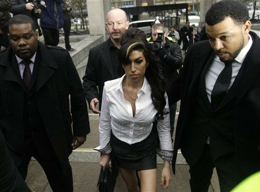 British singer Amy Winehouse, center, arrives at Magistrates Court in Milton Keynes, England, Wednesday, Jan. 20, 2010. Winehouse pleaded guilty Wednesday to assaulting a theater manager at a family Christmas show.  The 26-year-old admitted charges of disorder and common assault during a Dec. 19 performance of the pantomime, or variety show, &#34;Cinderella.&#34;  &#40;AP Photo&#47;Matt Dunham&#41; <span class=meta>(AP Photo&#47; Matt Dunham)</span>