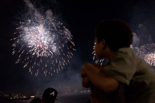 Spectators watch the annual Independence Day fireworks over the Hudson River, Monday, July 4, 2011, in New York. A portion Manhattan&#39;s west side is closed to vehicular traffic, allowing pedestrians to camp out and wait for the 40,000 shells launched after dusk from a barge on the river. &#40;AP Photo&#47;John Minchillo&#41; <span class=meta>(AP Photo&#47; John Minchillo)</span>