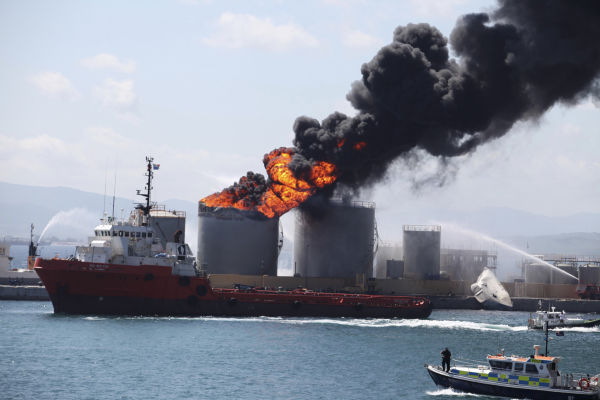 Flames and smoke billow from an oil tank in the docks of Gibraltar, Tuesday May 31, 2011. The cause of the explosion was not immediately known but two people were reported injured. &#40;AP Photo&#47;Alicia Jimenez&#41; <span class=meta>(AP Photo&#47; Alicia Jimenez)</span>