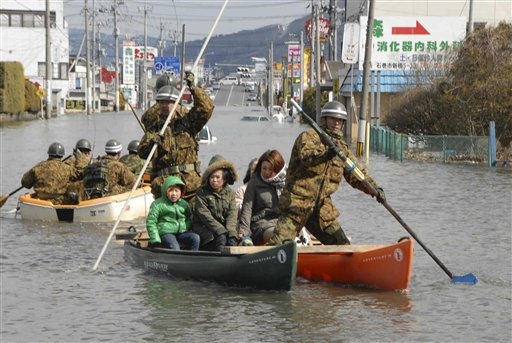Japan Defense Force personell help people go through the flooded area by boats in Ishinomaki in Miyagi Prefecture &#40;state&#41;, northern Japan, Saturday morning, March 12, 2011, a day after a strong earthquake-triggered devastating tsunami hit the area. &#40;AP Photo&#47;The Yomiuri Shimbun&#41;  JAPAN OUT, CREDIT MANDATORY <span class=meta>(AP Photo&#47; Anonymous)</span>