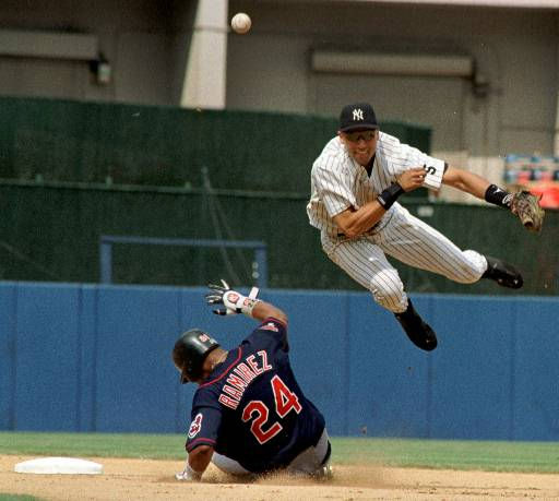 New York Yankees&#39; Derek Jeter completes a sixth inning double play as Cleveland Indians Manny Ramirez slides into second as the Yankees won 2-1 at Yankee Stadium in New York, Sunday, July 25, 1999. &#40;AP Photo&#47;Osamu Honda&#41; <span class=meta>(AP Photo&#47; OSAMU HONDA)</span>