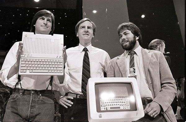 In this April 24, 1984, file photo, from left, Steve Jobs, chairman of Apple Computers, John Sculley, president and CEO, and Steve Wozniak, co-founder of Apple, unveil the new Apple IIc computer in San Francisco. Apple on Wednesday, Oct. 5, 2011 said Jobs has died. He was 56. <span class=meta>(AP Photo)</span>