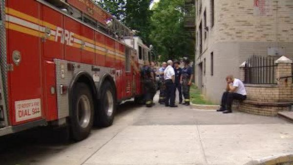 Firefighters rush into a burning apartment in the Bronx
