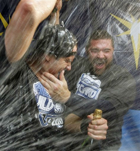 Tampa Bay Rays&#39; Evan Longoria, left, and Kelly Shoppach celebrate with champagne early Thursday, Sept. 29, 2011, after the Rays defeated the New York Yankees 8-7 in a baseball game and clinched the AL wild card in St. Petersburg, Fla. &#40;AP Photo&#47;Mike Carlson&#41; <span class=meta>(AP Photo&#47; Mike Carlson)</span>