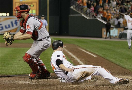 Baltimore Orioles&#39; Nolan Reimold slides into home plate next to Boston Red Sox&#39;s Ryan Lavarnway to score the winning run in the ninth inning of a baseball game on Wednesday, Sept. 28, 2011, in Baltimore. Baltimore won 4-3. &#40;AP Photo&#47;Patrick Semansky&#41; <span class=meta>(AP Photo&#47; Patrick Semansky)</span>