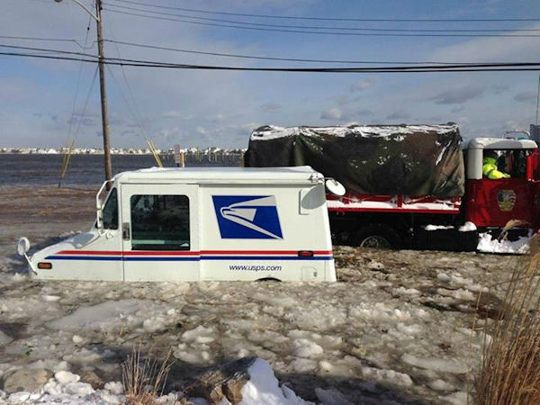 Crews from the Monmouth Beach and Long Branch Fire Departments rescued a mailman as the Shrewsbury River surrounded his truck at the intersection of North Road and Shrewsbury Drive.  <span class=meta>(Monmouth County Sheriffs Office.)</span>