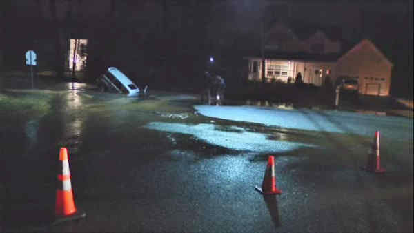 A large sinkhole in Long Island swallowed up a car that a New York postal worker was driving in.