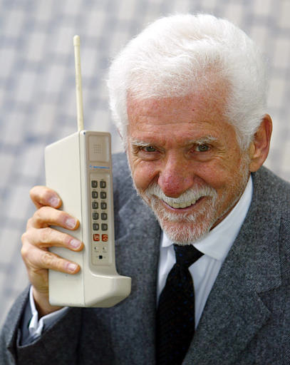 Martin Cooper, chairman and CEO of ArrayComm, holds a Motorola DynaTAC, a 1973 prototype of the first handheld cellular telephone in San Francisco, Wednesday April 2, 2003. 30 years ago the first call was made from a handheld cellular telephone.(AP Photo/Eric Risberg)