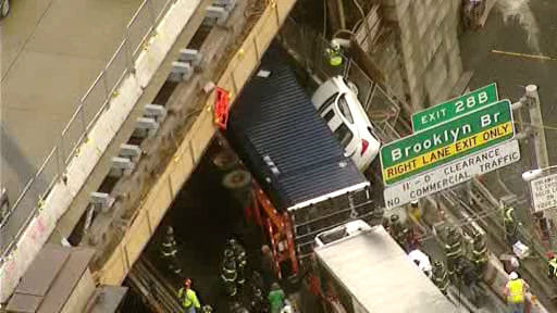 An overturned truck pinned a car against the side of the Brooklyn-Queens Expressway at the Brooklyn Bridge on Monday, April 29, 2013.
