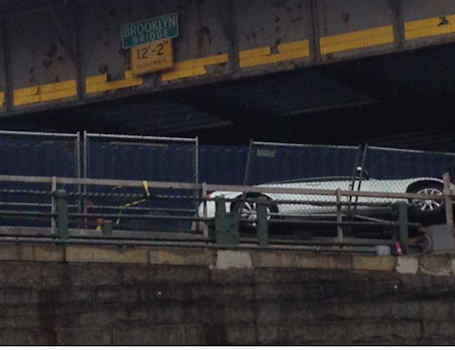 An overturned truck that pinned a car against the side of the Brooklyn-Queens Expressway at the Brooklyn Bridge.