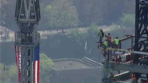 Photos of the final pieces of the spire being raised to the roof of One World Trade Center.