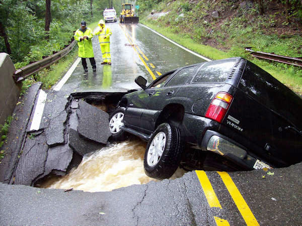 The driver of this SUV was driving on Kinnelon Road in Kinnelon at 8:40 Sunday morning when the road collapsed.  The 39-year-old woman was able to escape the GMC Yukon and get a ride from another motorist.   <span class=meta>(Photo&#47;Kinnelon Police Department)</span>