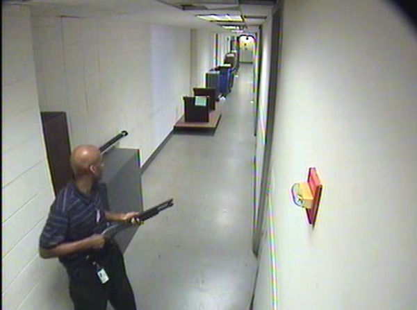 Alexis moves through the hallways of Building #197 carrying the Remington 870 shotgun. <span class=meta>(FBI)</span>
