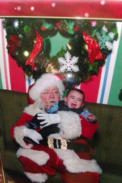 Santa appears to have his hands full with this young man!