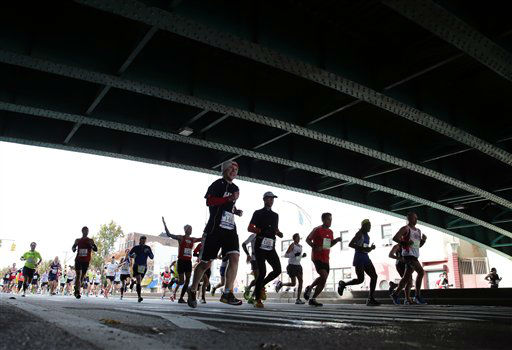 Runners pass under a bridge on Fourth Avenue in the Brooklyn borough of New York during the New York City Marathon, Sunday, Nov. 3, 2013. (AP Photo/Peter Morgan)