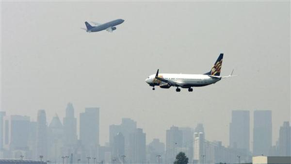 An airplane descends for landing as another takes off at La Guardia Airport. (AP Photo)